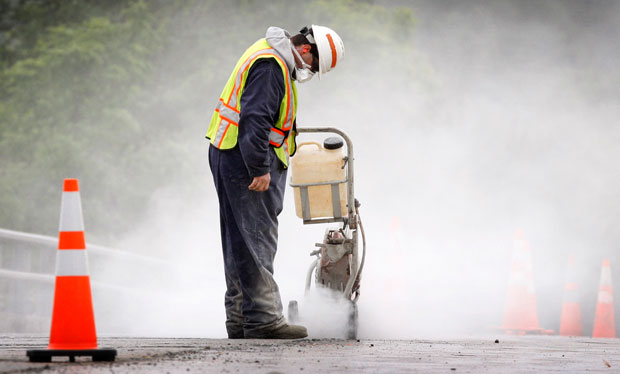 A transportation worker creates a dust cloud while cutting concrete