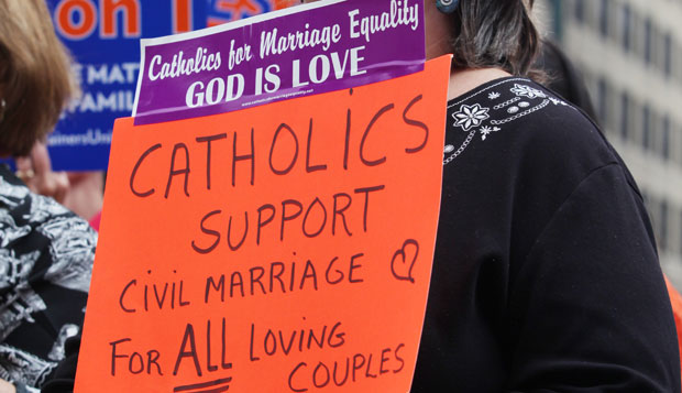 Catholic support of gay marriage holds sign saying so